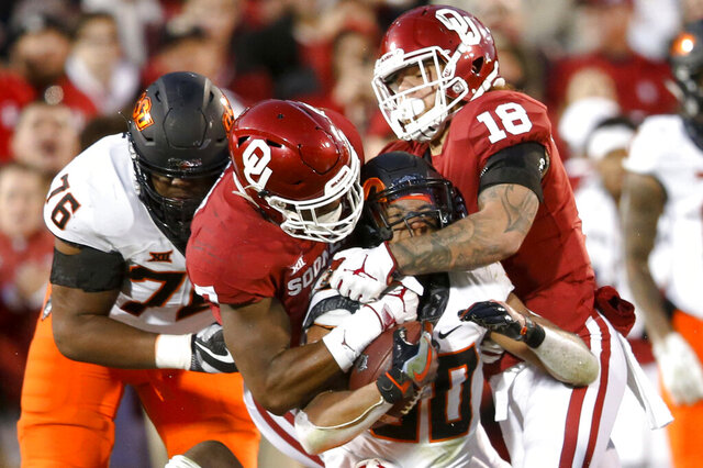 FILE - In this Nov. 10, 2018, file photo, Oklahoma defensive end Ronnie Perkins (7) and linebacker Curtis Bolton (18) tackle Oklahoma State running back Chuba Hubbard (30) during an NCAA college football game in Norman, Okla. The Bedlam rivalry between No. 7 Oklahoma and No. 21 Oklahoma State is back at the end of the regular season after earlier November dates the past two seasons. (Ian Maule/Tulsa World via AP, File)
