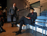 FILE - In this Oct. 3, 2018, file photo, Hockey Hall of Famer Willie O'Ree, right, who was the first African-American hockey player in the NHL, sits briefly in a replica of seats from Ebbets Field, in front of a large photograph of Jackie Robinson's first game, during a tour of the Smithsonian's National Museum of African American History and Culture with NHL commissioner Gary Bettman, left, in Washington. Through his work as the NHL's diversity ambassador over the past 20 years, O'Ree has tried to work toward more inclusion and better minority representation.  (AP Photo/Jacquelyn Martin, File)