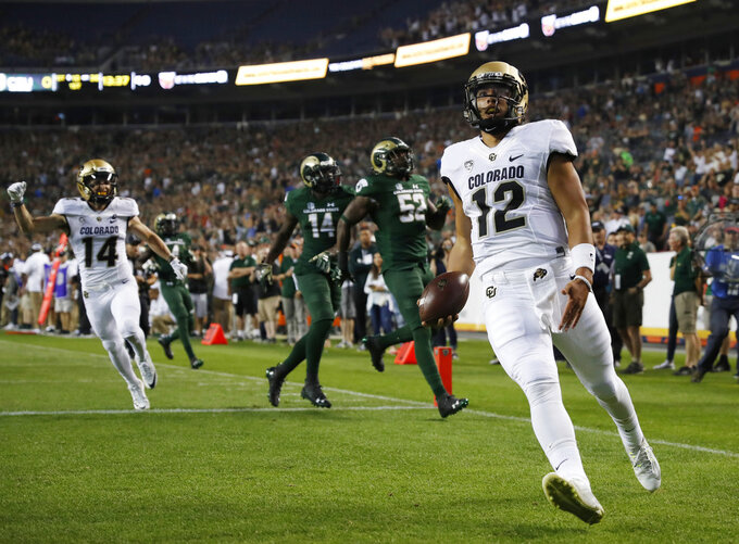 Colorado quarterback Steven Montez, front,  runs for a toucdown against Colorado State in the first half of an NCAA college football game Friday, Aug. 31, 2018, in Denver. (AP Photo/David Zalubowski)