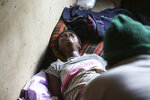 Samantha Nazarere goes into labor in a tiny apartment in the poor Mbare suburb in Harare, Zimbabwe, Saturday, Nov. 16, 2019, to deliver a baby boy with the help of 72-year old grandmother Esther Zinyoro Gwena.  Grandmother Esther Zinyoro Gwena claims to be guided by the holy spirit and has become a local hero, as the country's economic crisis forces closure of medical facilities, and mothers-to-be seek out untrained birth attendants.(AP Photo/Tsvangirayi Mukwazhi)