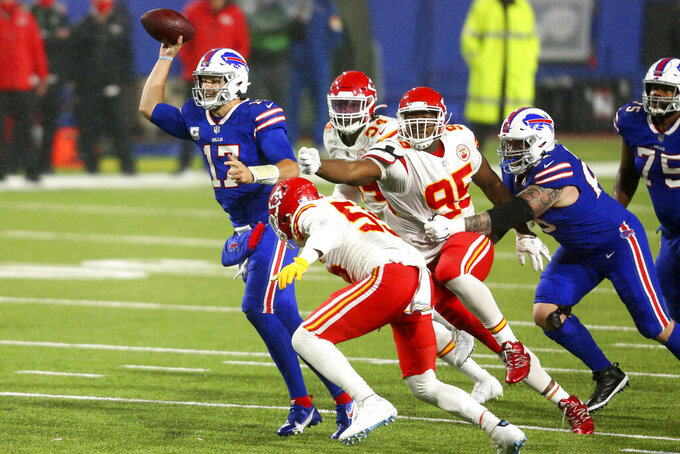 Buffalo Bills quarterback Josh Allen, left, tries to evade Kansas City Chiefs defenders during the second half of an NFL football game, Monday, Oct. 19, 2020, in Orchard Park, N.Y. (AP Photo/Jeffrey T. Barnes)