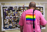 "This July 4, 2019 photo shows a man viewing a memorial panel during the International Association of Gay Square Dance Clubs  annual convention in Philadelphia. 850 square dancers participated in the annual convention last week in a Philadelphia hotel, bringing their best promenades and do-si-dos to a slightly sped-up version of ""Somewhere Over the Rainbow."" (AP Photo/Jacqueline Larma)"