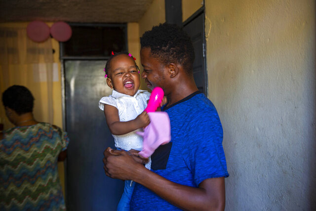 Verty holds up his 1-year-old daughter at his house in Port-au-Prince, Haiti, Tuesday, Aug. 25, 2020. The Trump administration has sharply increased its use of hotels to detain immigrant children before expelling them from the United States during the coronavirus pandemic. Verty says government contractors at a hotel where he was detained gave his family, including his daughter, cups of ice to eat to pass temperature checks prior to their deportation flight, even though they had tested negative for COVID-19. (AP Photo/Dieu Nalio Chery)