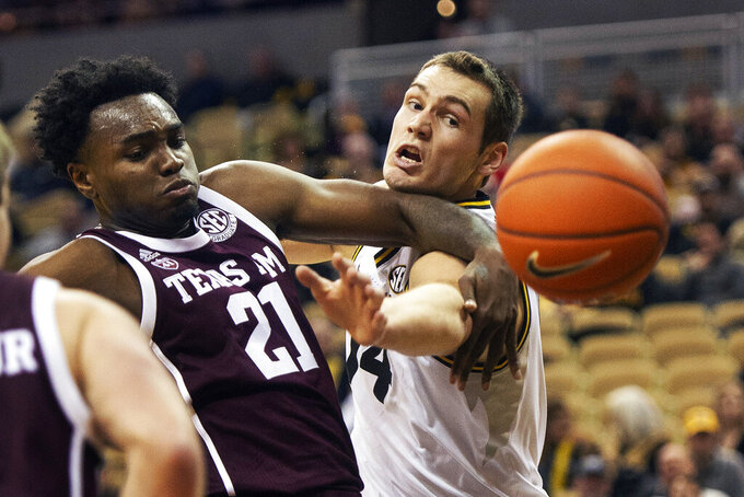 Missouri's Reed Nikko, right, and Texas A&M's Christian Mekowulu, left, battle for a rebound during the first half of an NCAA college basketball game, Saturday, Feb. 9, 2019, in Columbia, Mo. (AP Photo/L.G. Patterson)