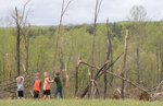 Damaged trees and children frame the property where Delores Anderson's house on Windy Ridge Road in Franklin County was leveled by a tornado Friday, April 19, 2019. From left to right, Bryce Powell, 3, Cooper Altice, 7, Jackson Anderson, 6, and Hunter Powell 8. (Heather Rousseau/The Roanoke Times via AP)