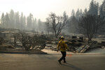 FILE - In this Friday, Nov. 16, 2018, file photo, a firefighter searches for human remains in a trailer park destroyed in the Camp Fire, in Paradise, Calif. Pacific Gas and Electric says it has reached a $13.5 billion settlement that will resolve all major claims related to devastating wildfires blamed on its outdated equipment and negligence. The settlement, which the utility says was reached Friday, Dec. 6, 2019, still requires court approval. (AP Photo/John Locher, File)