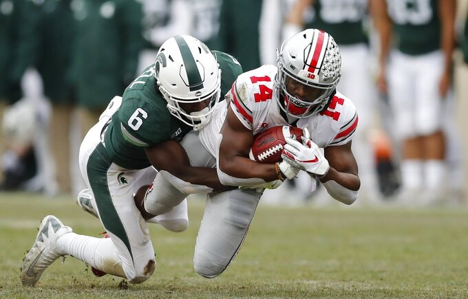 Ohio State wide receiver K.J. Hill (14) is tackled by Michigan State safety David Dowell (6) during the first half of an NCAA college football game, Saturday, Nov. 10, 2018, in East Lansing, Mich. (AP Photo/Carlos Osorio)