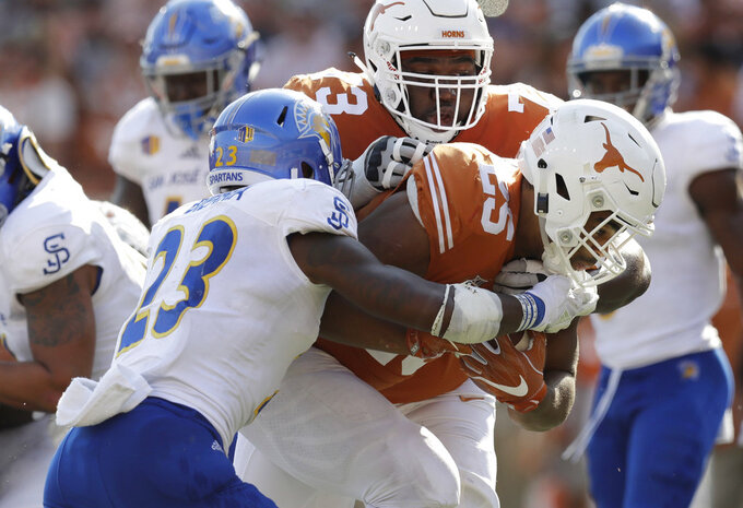 FILE - In this Sept. 9, 2017, file photo, Texas running back Chris Warren III (25) scores a touchdown past San Jose State safety Trevon Bierria (23) with the help of teammate Patrick Hudson (73) during the second half of an NCAA college football game  in Austin, Texas. Hudson was taken to a hospital and treated in intensive care this week because of a heat-related illness at practice, coach Tom Herman said Thursday, Sept. 6, 2018. (AP Photo/Eric Gay, File)
