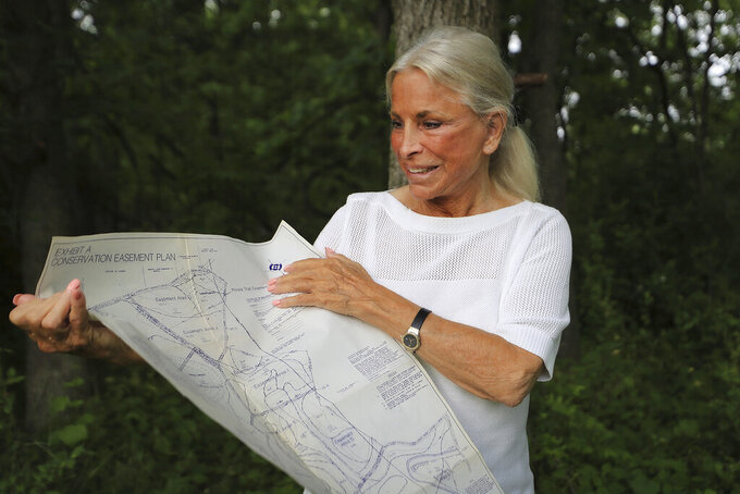 Carol McCloskey, of Newtown Square, looks over a property map of a plot of land in the Brandywine Valley in Chester County, Pa. , on Thursday, June 3, 2021. McCloskey has owned a half acre plot on what's known as Indian Knoll and designated by the county as a historical Native American burial site of the Lenape. She is 78 and wants to donate it to a tribe, but can't find a taker. (David Maialetti/The Philadelphia Inquirer via AP)