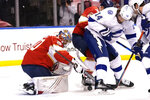 Florida Panthers goaltender Spencer Knight, left, goes against Tampa Bay Lightning left wing Pat Maroon (14) as he stops a shot on the goal during the first period in Game 5 of an NHL hockey Stanley Cup first-round playoff series, Monday, May 24, 2021, in Sunrise, Fla. (AP Photo/Lynne Sladky)