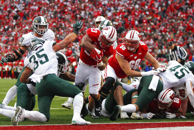 Wisconsin running back Jonathan Taylor (23) scores a touchdown against Michigan State linebacker Joe Bachie (35) during the second half of an NCAA college football game Saturday, Oct. 12, 2019, in Madison, Wis. Wisconsin won 38-0. (AP Photo/Andy Manis)