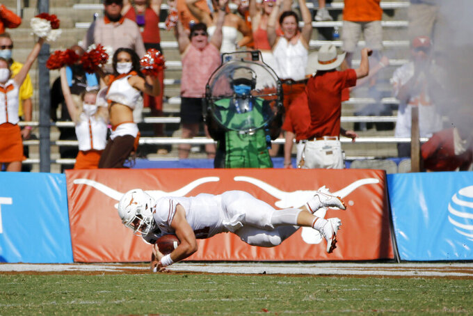 Texas quarterback Sam Ehlinger (11) scores a touchdown against Oklahoma during an NCAA college football game in Dallas, Saturday, Oct. 10, 2020. (AP Photo/Michael Ainsworth)