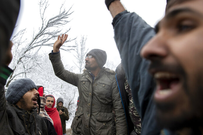 Migrants chant as they gather in protest of conditions at the Vucjak refugee camp outside Bihac, northwestern Bosnia, Tuesday, Dec. 3, 2019. Despite calls for their relocation before winter, hundreds of migrants remain stuck in a make-shift tent camp in northwestern Bosnia as a spate of snowy and cold weather hit the region. (AP Photo/Darko Bandic)