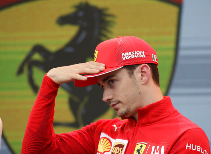 Ferrari driver Charles Leclerc of Monaco gestures during an autographs session at the Monaco racetrack, in Monaco, Friday, May 24, 2019. The Formula one race will be held on Sunday. (AP Photo/Luca Bruno)