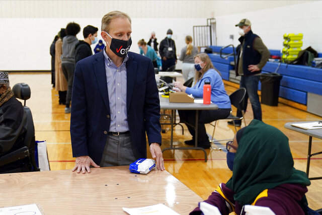 Minnesota Secretary of State Steve Simon visits with poll workers as he toured the Brian Coyle Center, Election Day Tuesday, Nov. 3, 2020, in Minneapolis. (AP Photo/Jim Mone)