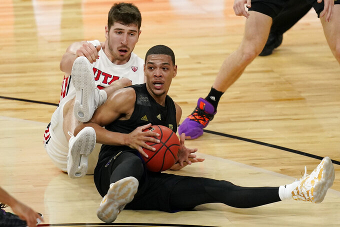 Washington's Quade Green, right, scrambles for the ball with Utah's Riley Battin (21) during the first half of an NCAA college basketball game in the first round of the Pac-12 men's tournament Wednesday, March 10, 2021, in Las Vegas. (AP Photo/John Locher)