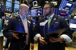Traders Patrick Casey, left, and Ryan Falvey confer on the floor of the New York Stock Exchange, Monday, Nov. 4, 2019. Stocks are opening higher on Wall Street, pushing major indexes toward more record highs. (AP Photo/Richard Drew)