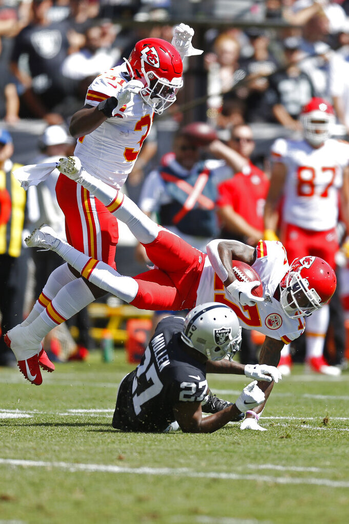 Kansas City Chiefs wide receiver Mecole Hardman carries the ball over Oakland Raiders cornerback Trayvon Mullen (27) during the first half of an NFL football game Sunday, Sept. 15, 2019, in Oakland, Calif. At left is Kansas City Chiefs running back Darrel Williams (31). (AP Photo/D. Ross Cameron)