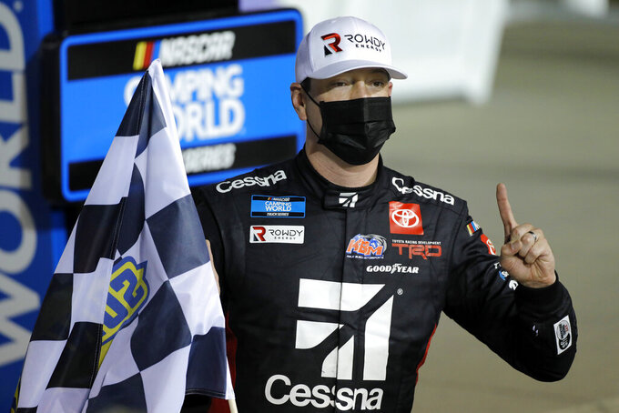 Kyle Busch poses for photos in victory lane after winning a NASCAR Truck Series auto race at Kansas Speedway in Kansas City, Kan., Saturday, May 1, 2021. (AP Photo/Colin E. Braley)