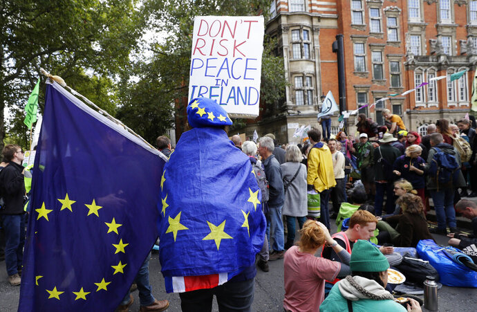 An Anti-Brexit demonstrator joins climate demonstrators near Parliament in London, Tuesday, Oct. 8, 2019. The British government said Tuesday that the chances of a Brexit deal with the European Union were fading fast, as the two sides remained unwilling to shift from their entrenched positions. (AP Photo/Kirsty Wigglesworth)