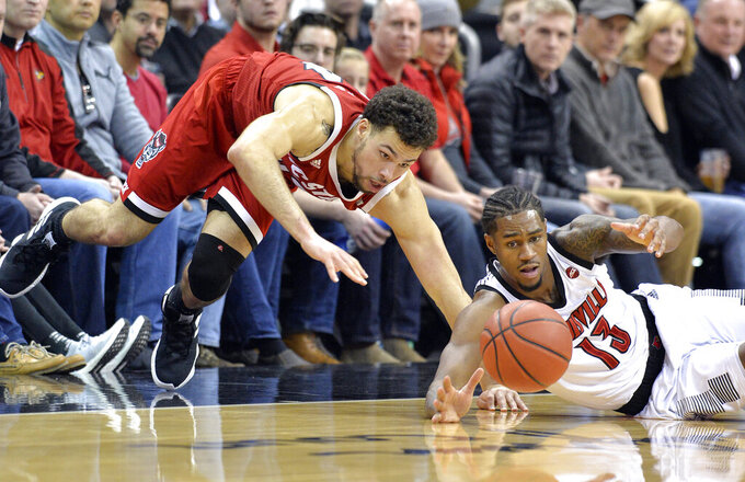 North Carolina State guard Devon Daniels, left, and Louisville forward V.J. King (13) watch the ball bound away during the first half of an NCAA college basketball game in Louisville, Ky., Thursday, Jan. 24, 2019. (AP Photo/Timothy D. Easley)