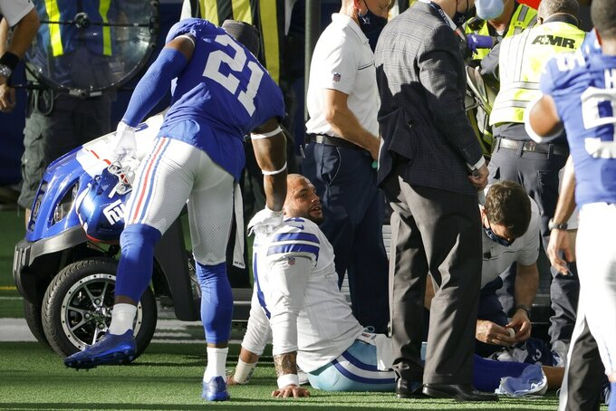 New York Giants safety Jabrill Peppers (21) comforts Dallas Cowboys quarterback Dak Prescott, bottom center, who receives medical attention after suffering a lower right leg injury in the second half of an NFL football game in Arlington, Texas, Sunday, Oct. 11, 2020. (AP Photo/Ron Jenkins)