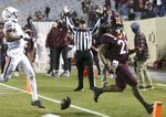 Virginia Tech's Khalil Herbert, right, drops the ball after scoring a touchdown against Virginia during the first half of an NCAA college football game Saturday, Dec. 12, 2020, in Blacksburg, Va. (Matt Gentry/The Roanoke Times via AP, Pool)