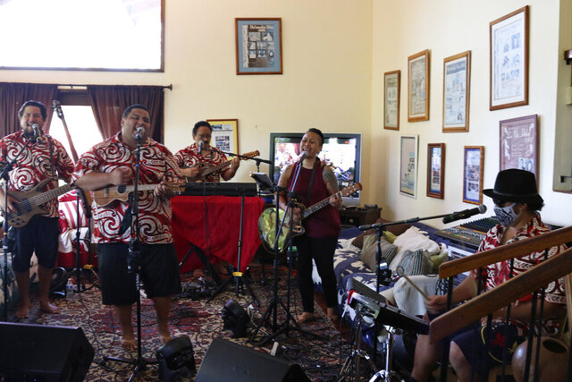 In this May 5, 2020, photo Kanilau, the Chang family's band, plays music for a livestream performance from the living room of Roland Chang's home in Honolulu. The coronavirus pandemic has taken out large sections of Hawaii's tourism-based economy, including the Chang family's turtle and dolphin snorkel tour business and their regular music gig in Waikiki. (AP Photo/Audrey McAvoy)