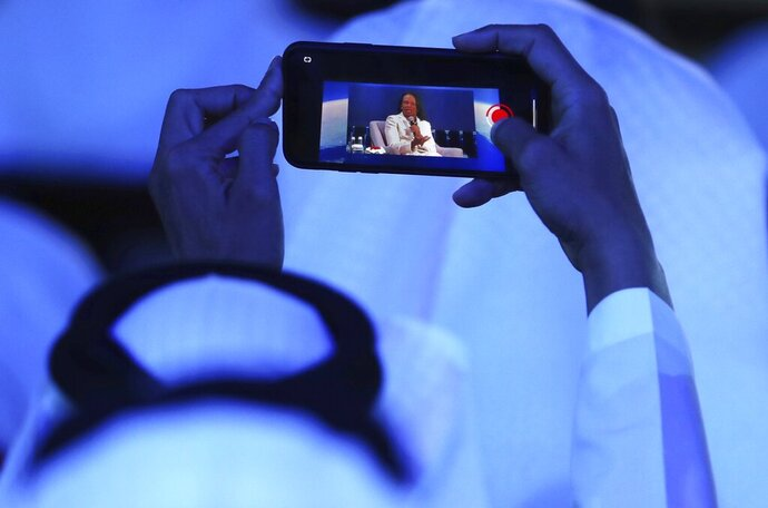 An Emirati man takes video of former US Secretary of State, Condoleezza Rice on his mobil phone at the opening ceremony of the Abu Dhabi International Petroleum Exhibition & Conference, ADIPEC, in Abu Dhabi, United Arab Emirates. (AP Photo/Kamran Jebreili)