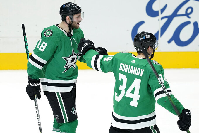 Dallas Stars' Jason Dickinson (18) and Denis Gurianov (34) celebrate an overtime goal scored by Dickinson that gave the team a 2-1 win over the Detroit Red Wings in an NHL hockey game in Dallas, Tuesday, Jan. 26, 2021. (AP Photo/Tony Gutierrez)