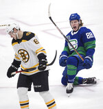 Vancouver Canucks' Adam Gaudette, right, celebrates after scoring a goal, as Boston Bruins' Anton Blidh, of Sweden, skates to the bench during the second period of an NHL hockey game Saturday, Feb. 22, 2020, in Vancouver, British Columbia. (Darryl Dyck/The Canadian Press via AP)