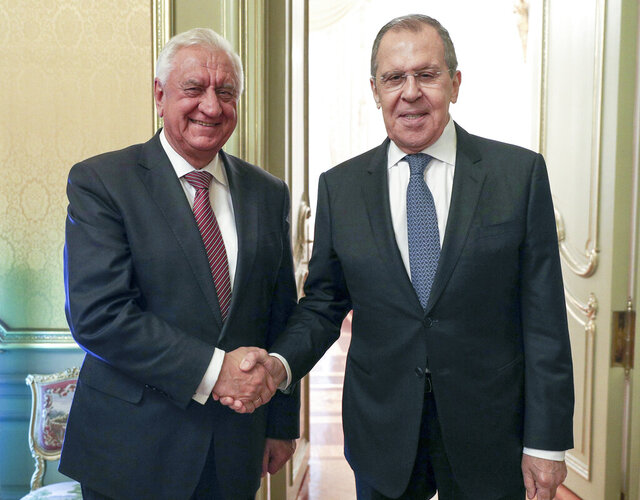 In this photo released by the Russian Foreign Ministry Press Service, Russian Foreign Minister Sergey Lavrov, right, and Chairman of the Board of the Eurasian Economic Commission Mikhail Myasnikovich pose for a photo prior to the talks in Moscow, Russia, Tuesday, Sept. 22, 2020. (Russian Foreign Ministry Press Service via AP)