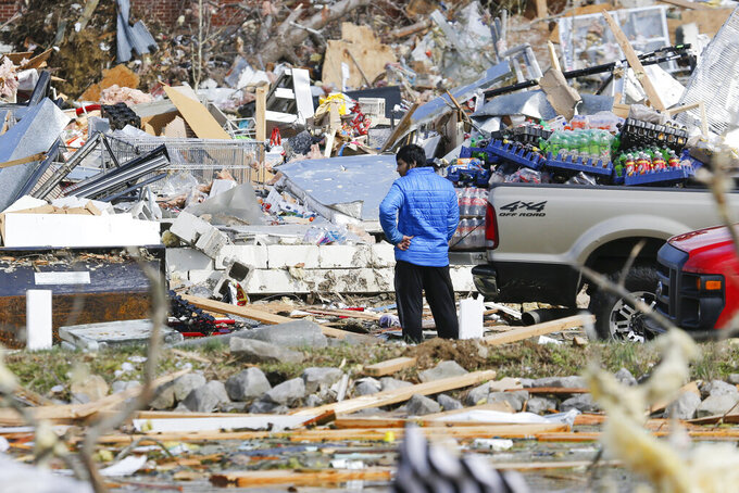 A man looks for items he can salvage from his store Tuesday, March 3, 2020, near Cookeville, Tenn. Tornadoes ripped across Tennessee early Tuesday, shredding more than 140 buildings and burying people in piles of rubble and wrecked basements. At least 22 people were killed. (AP Photo/Mark Humphrey)