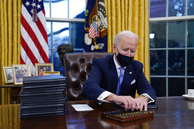 FILE - In this Jan. 20, 2021, file photo, President Joe Biden reaches for a pen to sign his first executive order in the Oval Office of the White House in Washington. Biden arrived at the White House ready to wield his pen to dismantle Donald Trump's legacy and begin pushing his own priorities. (AP Photo/Evan Vucci, File)