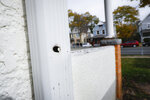 In this Oct. 23, 2019, photo, a bullet hole in a drainage vent cited in a crime scene investigation follows a trajectory towards the former home, in blue, of Tyesha Edwards, an 11-year-old girl pierced in the heart by a stray bullet in 2002 while doing homework at her family's dining room table in Minneapolis. Myon Burrell, a black teenager convicted for the killing with no gun, fingerprints or hard evidence implicating him, has drawn a growing number of legal experts, community leaders and civil rights activists who are worried that he may have been wrongly convicted. (AP Photo/John Minchillo)