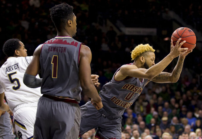 Boston College's Ky Bowman (0) grabs a rebound next to Notre Dame's D.J. Harvey (5) during the second half of an NCAA college basketball game Saturday, Jan. 12, 2019, in South Bend, Ind. Notre Dame won 69-66. (AP Photo/Robert Franklin)