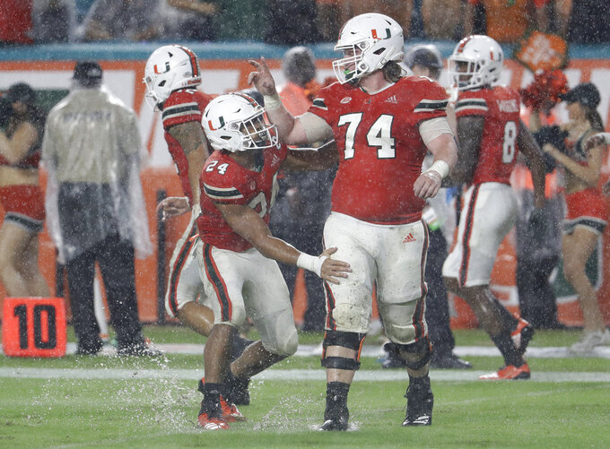 Miami running back Travis Homer (24) celebrates with offensive lineman Tyler Gauthier (74) after scoring a touchdown during the first half of an NCAA college football game against Duke, Saturday, Nov. 3, 2018, in Miami Gardens, Fla. (AP Photo/Lynne Sladky)