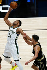 Milwaukee Bucks forward Giannis Antetokounmpo (34) reaches for the ball next to Atlanta Hawks guard Bogdan Bogdanovic (13) during the first half of an NBA basketball game Thursday, April 15, 2021, in Atlanta. (AP Photo/John Bazemore)