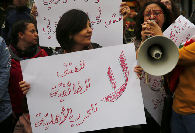 Lebanese women shout slogans, as they hold an Arabic placard that reads: