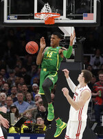 Oregon forward Kenny Wooten (14) reacts after dunking over Wisconsin forward Ethan Happ during the second half of a first-round game in the NCAA men's college basketball tournament, Friday, March 22, 2019, in San Jose, Calif. (AP Photo/Chris Carlson)