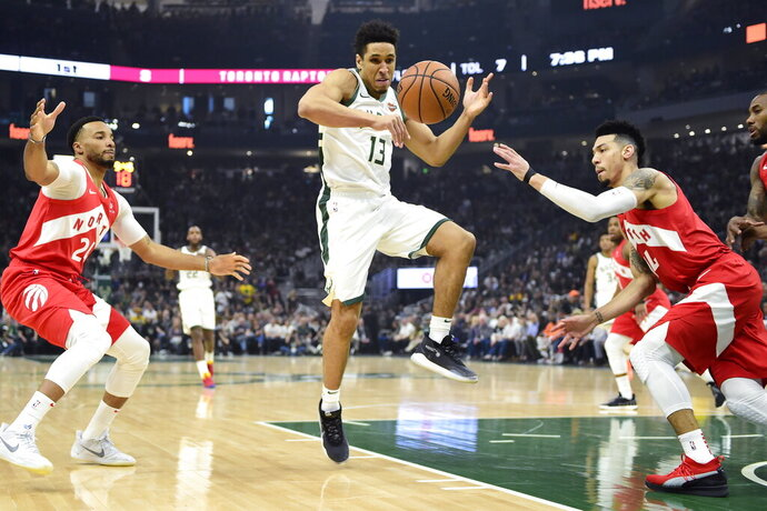 Milwaukee Bucks guard Malcolm Brogdon (13) loses the ball as Toronto Raptors forward Norman Powell (24) and guard Danny Green (14) defend during the first half of Game 5 of the NBA basketball playoffs Eastern Conference finals in Milwaukee on Thursday, May 23, 2019. (Frank Gunn/The Canadian Press via AP)