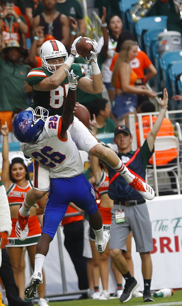 Miami tight end Will Mallory scores a touchdown against Savannah State defensive back Darrell Bonner during the first half an NCAA college football game, Saturday, Sept. 8, 2018, in Miami Gardens. (AP Photo/Brynn Anderson)