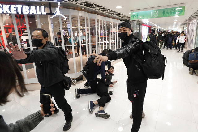 An undercover policeman points a can of pepper spray as others detain a protester during a demonstration at a shopping mall popular with traders from mainland China near the Chinese border in Hong Kong, Saturday, Dec. 28, 2019. Protesters shouting