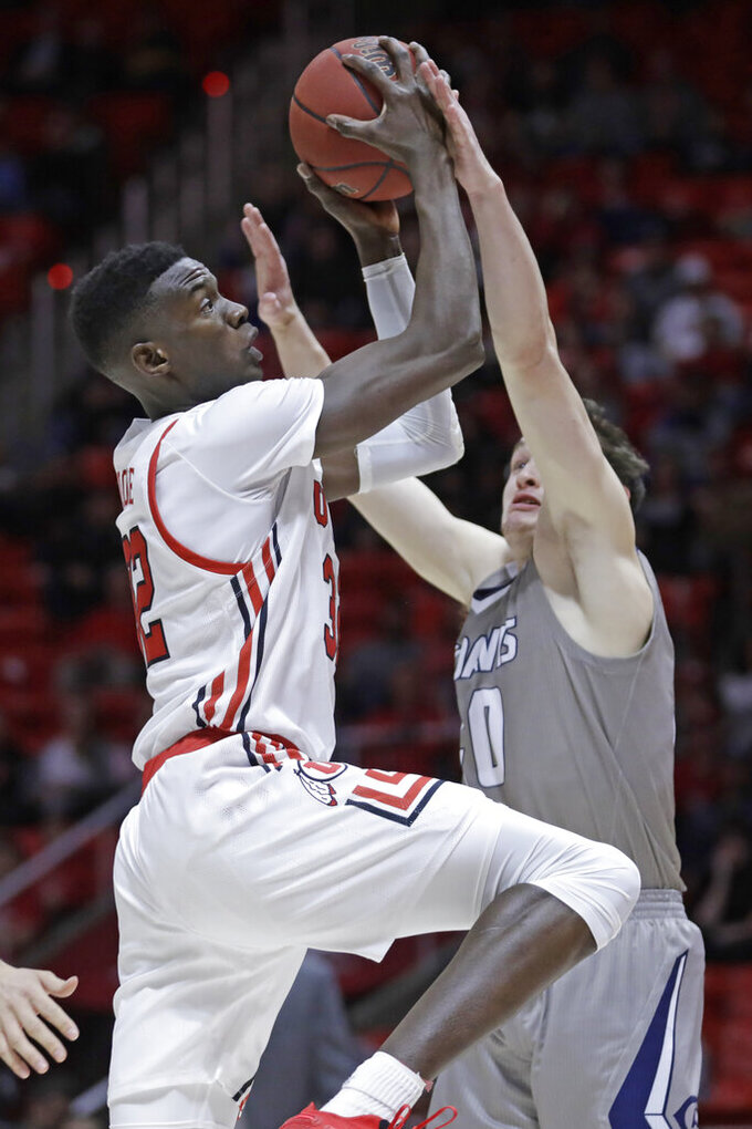 Utah center Lahat Thioune, left, goes to the basket as UC Davis guard Elijah Pepper (40) defends during the second half of an NCAA college basketball game Friday, Nov. 29, 2019, in Salt Lake City. (AP Photo/Rick Bowmer)