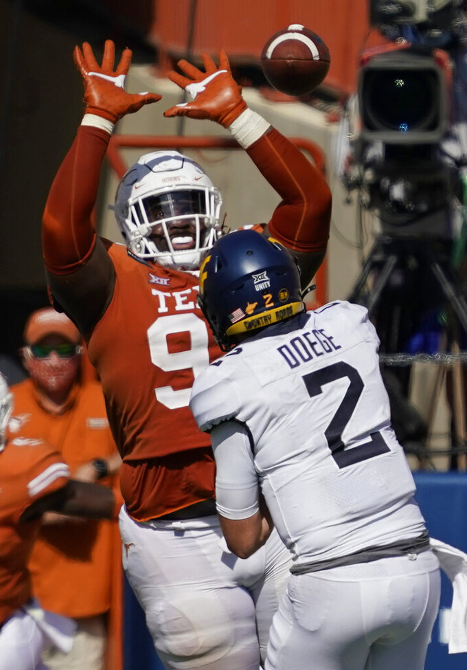 Texas' T'Vondre Sweat (93) blocks a pass by West Virginia's Jarret Doege (2) during the second half of an NCAA college football game in Austin, Texas, Saturday, Nov. 7, 2020. (AP Photo/Chuck Burton)