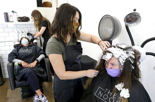 Daphne Jackson works on Shelby White as stylists at The Nook on 7th Street in Tuscaloosa, Ala., do hair Monday, May 11, 2020, for the first time since mid-March, when personal contact businesses were shut down due to COVID-19 restrictions. (Gary Cosby Jr./The Tuscaloosa News via AP)