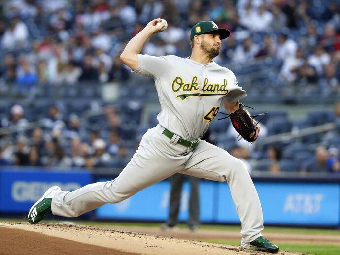 FILE - In this May 11, 2018, file photo, Oakland Athletics' Kendall Graveman delivers a pitch during the first inning of the team's baseball game against the New York Yankees in New York. The Mariners have added another option for their rotation by agreeing to a one-year contract with Kendall Graveman that guarantees the right-hander $2 million as he returns from Tommy John surgery. (AP Photo/Frank Franklin II, File)