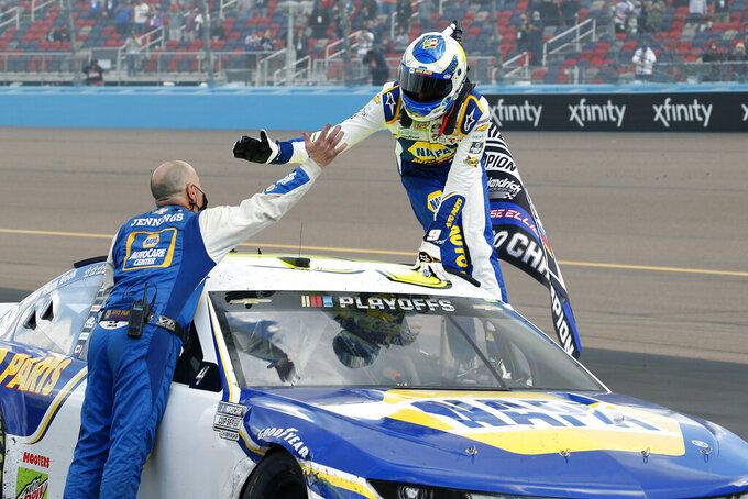 Chase Elliott, right, celebrates with a pit crew member following his season championship victory in the NASCAR Cup Series auto race at Phoenix Raceway, Sunday, Nov. 8, 2020, in Avondale, Ariz. (AP Photo/Ralph Freso)