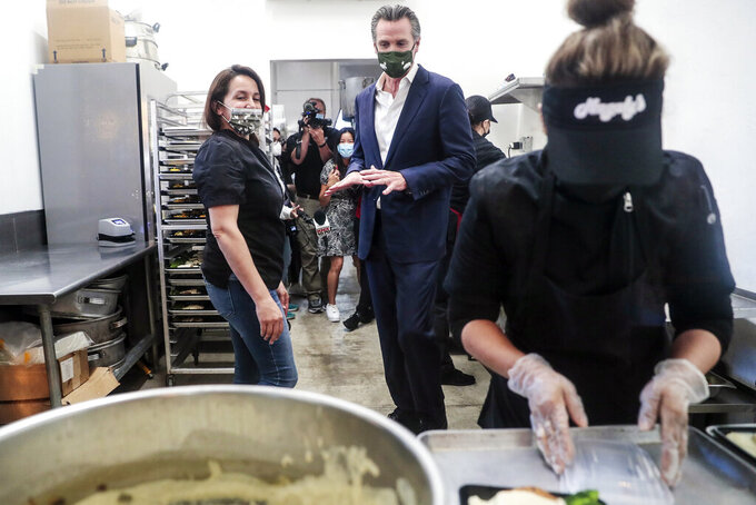 FILE - In this April 29, 2021, file photo, Elva Quinonez prepares food as California Gov. Gavin Newsom talks with Magaly Colelli at Magaly's restaurant in San Fernando, Calif. California is getting $27 billion from the federal government because of the coronavirus, and on Thursday, May 13, 2021, Gov. Newsom said he wants to give some of that money to small business owners that were forced to temporarily close during the coronavirus pandemic. (Robert Gauthier/Los Angeles Times via AP, Pool, File)