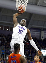 TCU forward Kouat Noi (12), of Australia, goes up to attempt a dunk as Florida center Kevarrius Hayes (13) and Noah Locke, rear, defend in the second half of an NCAA college basketball game in Fort Worth, Texas, Saturday, Jan. 26, 2019. Noi had a game-high 22 points in TCU's 55-50 win. (AP Photo/Tony Gutierrez)